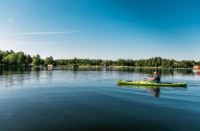 Man i båt som paddlar kajak