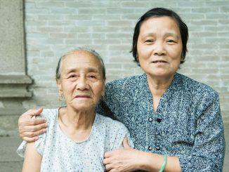 Två damer framför en stenvägg