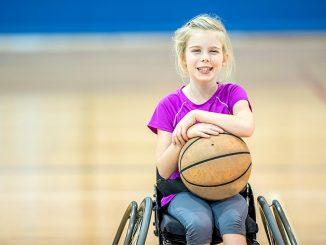 Rullstolsbunden flicka med basketboll
