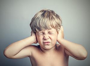 Pojke håller för öronen