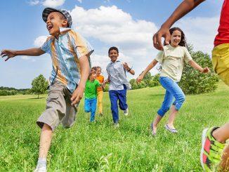 Barn springer över en äng